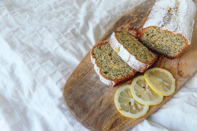 Pastel con semillas de amapola y ralladura de limón, espolvoreado con azúcar en polvo. magdalena con limón sobre una plancha de madera.