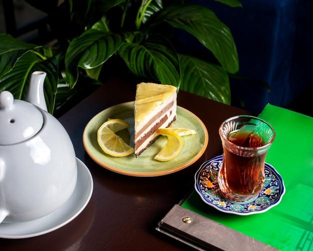 Pastel servido con rodajas de limón y té