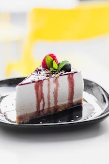 Pastel suave cubierto con frambuesa; menta; salsa de arándanos y chocolate servida en un plato negro contra un fondo borroso