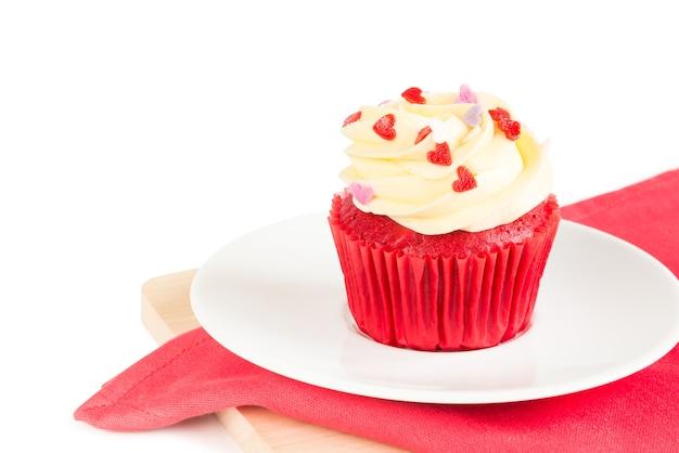 Pastel de taza de terciopelo rojo cubierto con glaseado en forma de corazón rojo, púrpura y rosa