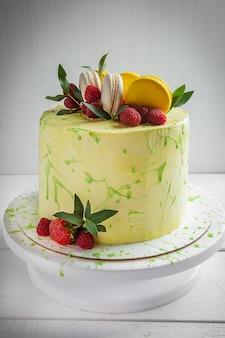 Pastel de té verde matcha con frambuesas de macarrón decorado con hojas verdes