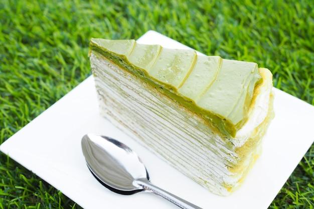 Pastel de té verde matcha en plato blanco sobre fondo verde hierba