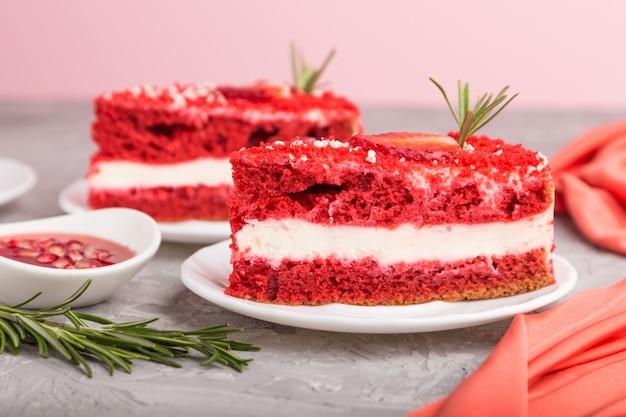 Pastel de terciopelo rojo casero con crema de leche y fresa sobre un fondo gris
