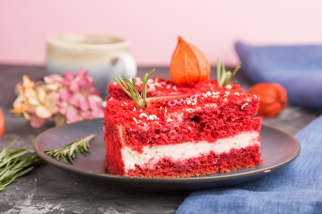 Pastel de terciopelo rojo casero con crema de leche y fresa con taza de café sobre un fondo de hormigón negro. vista lateral, enfoque selectivo.