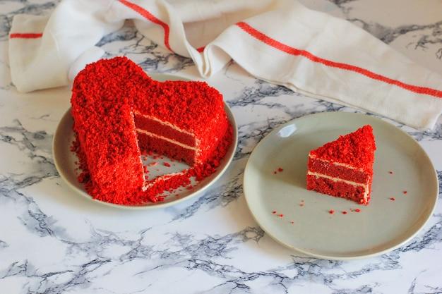 Pastel de terciopelo rojo en forma de corazón sobre la mesa de mármol.
