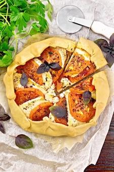Pastel con tomates, requesón y albahaca morada sobre pergamino, perejil sobre una tabla de madera de fondo desde arriba