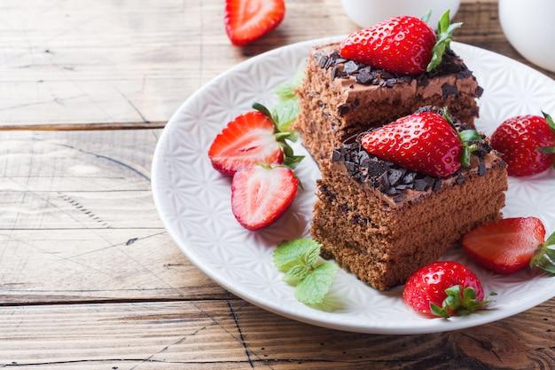 Pastel de trufa de chocolate con fresas y menta. mesa de madera. copia espacio