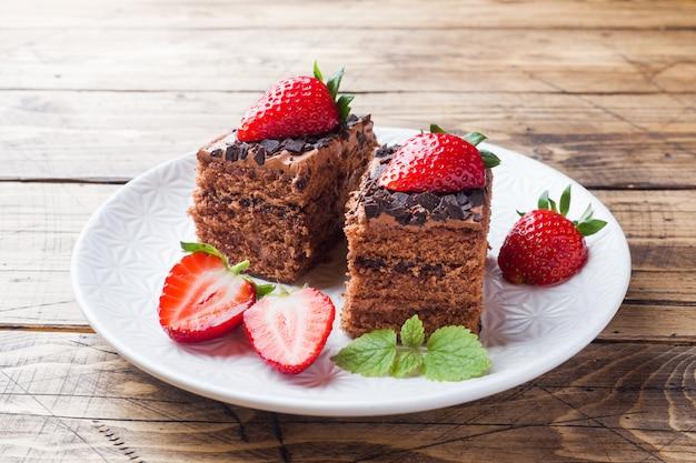 Pastel de trufa de chocolate con fresas y menta. mesa de madera.