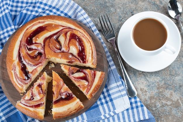 Un pastel de vainilla dulce con una taza de café.