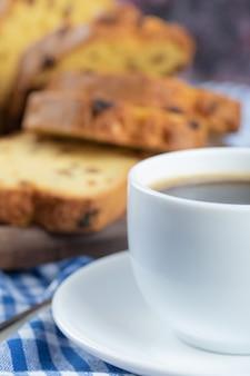 Un pastel de vainilla dulce con una taza de chocolate caliente.