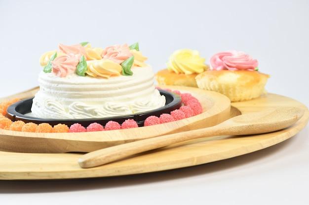Pastel de vainilla. maquillaje con hermosas flores puestas en el plato.