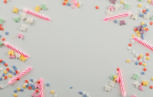 Pastel velas con chispitas de dulce sobre una mesa blanca