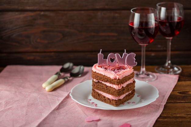 Pastel con velas y copas de vino.