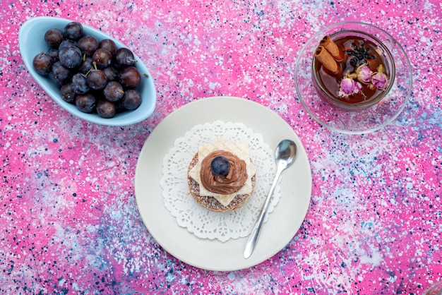 Pastel de vista superior con crema junto con frutis y té en el fondo de color pastel de frutas de color azúcar dulce
