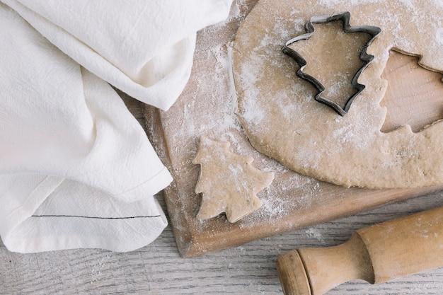 Pastelería cerca de cortador de galletas en tabla de cortar