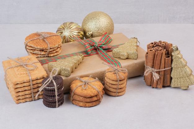 Pastelería en cuerda con regalo y bolas de navidad doradas sobre superficie blanca