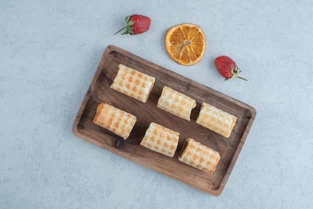Pastelería dulce con naranja seca y dos fresas sobre fondo de mármol