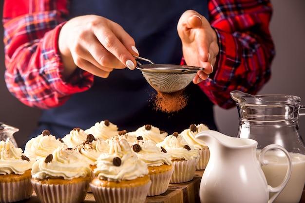 Pastelería femenina decora cupcakes con polvo de cacao tiramisú