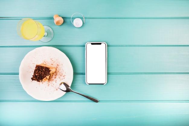Pastelería fresca con bebida y teléfono móvil en la mesa
