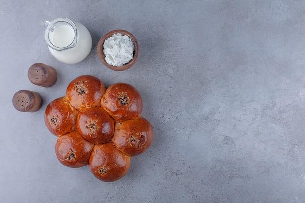 Pastelería fresca en forma de flor con crema y tarro de leche sobre fondo de piedra.