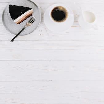 Pastelería fresca y taza de té para el desayuno en mesa de madera