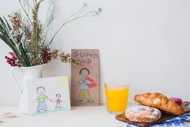 Pastelería y jugo cerca de dibujos y flores