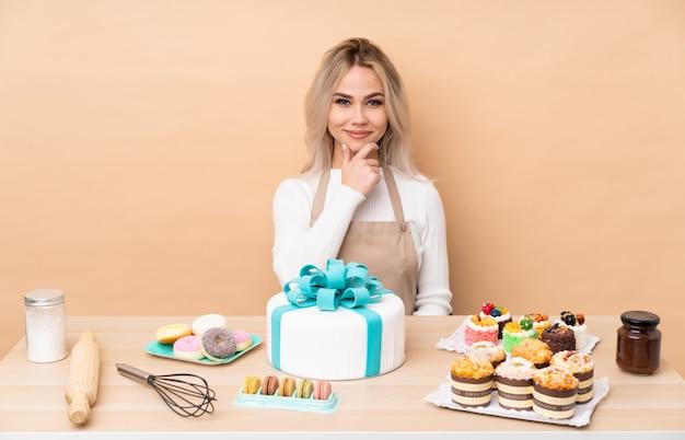 Pastelero adolescente con un gran pastel en una mesa riendo