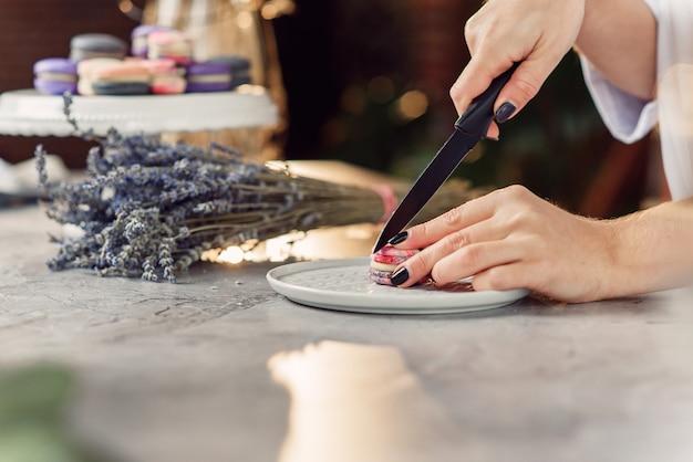 El pastelero corta el macarrón con un cuchillo. cerrar las manos del chef femenino. preparación de postre sabroso.