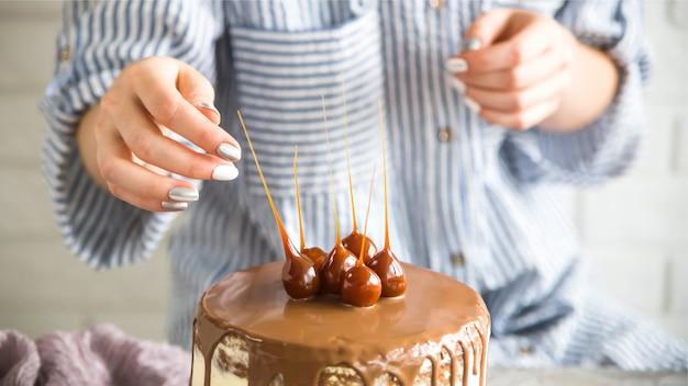 Un pastelero está decorando un pastel confeccionado.