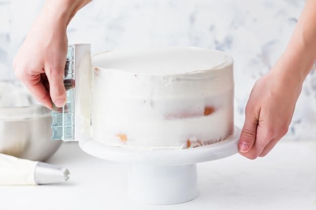 Pastelero haciendo pastel con crema blanca