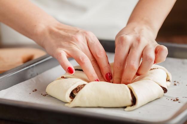 El pastelero moldea la masa con las manos para hacer galletas