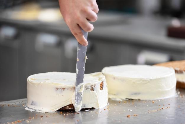 Pastelero profesional haciendo un delicioso pastel en la pastelería.
