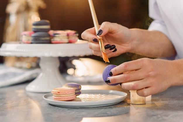 El pastelero profesional pinta con un pincel una comida de oro farb sobre un macarrón violeta fresco.