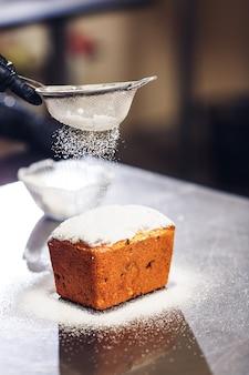 El pastelero rocía el pastel de pascua con azúcar glas a través del colador.