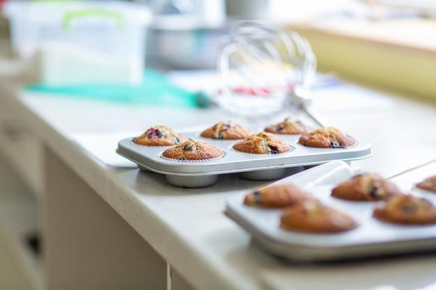 El pastelero sacó del horno muffins recién horneados en una fuente para hornear sobre la mesa