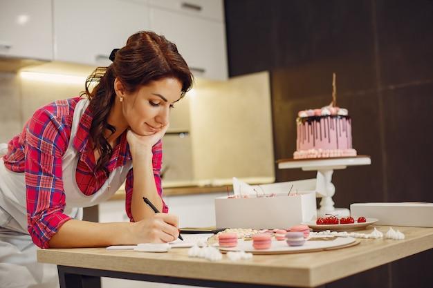 Pastelero en uniforme decora el pastel