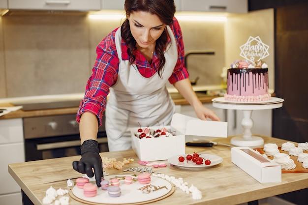 Pastelero en uniforme decora los pasteles