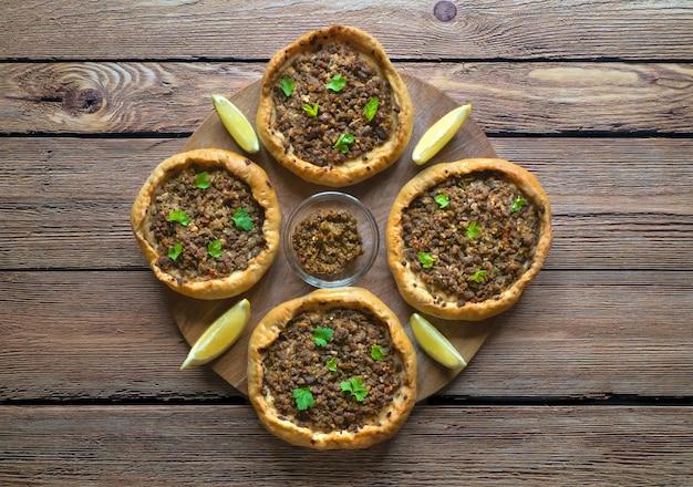 Los pasteles de carne árabes abiertos sfiha en tabla de cortar de madera.