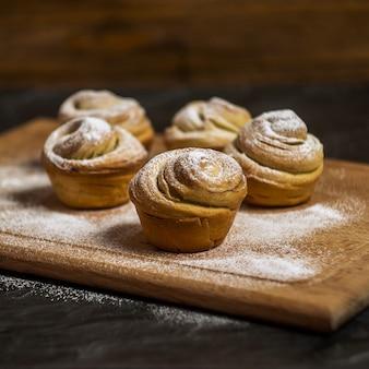 Pasteles caseros cruffins, muffins con azúcar en polvo, sobre escritorio de madera y oscuro, foco selectivo, cuadrado