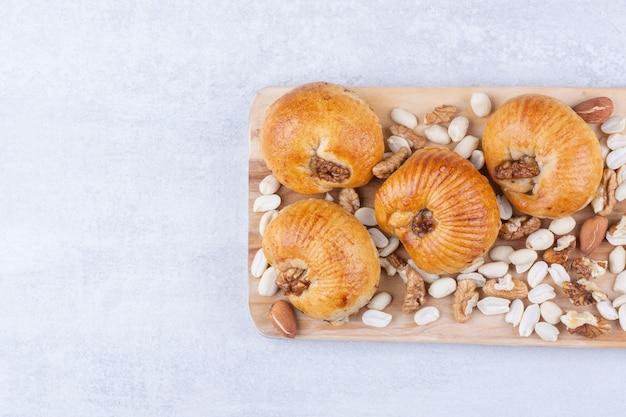 Pasteles dulces con granos sobre tabla de madera con diversas nueces