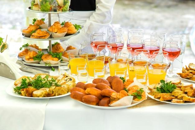 Pasteles, eclairs y bebidas en una mesa de banquete.