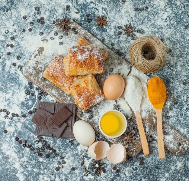 Pasteles con harina, chocolate, especias, huevos, vista superior de hilo en hormigón y tabla de cortar