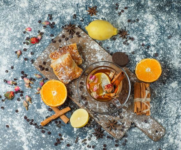 Pasteles con harina, té, choco, galletas, especias, limón, naranja, hierbas vista superior en hormigón y tabla de cortar