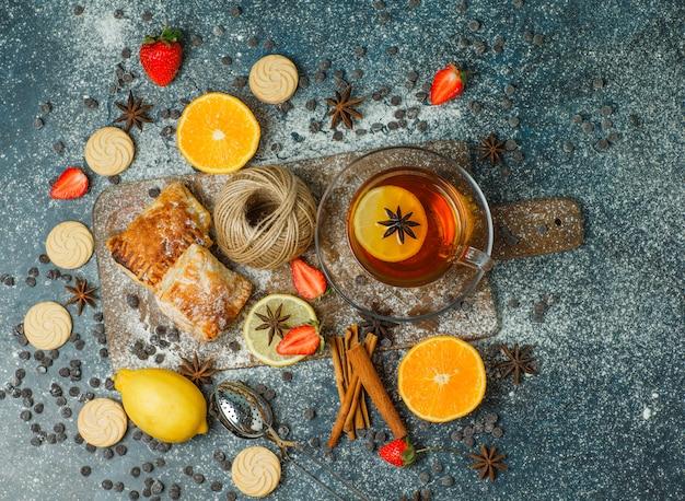 Pasteles con harina, té, frutas, galletas, chips de chocolate, especias, hilo sobre estuco y tabla de cortar, vista superior.