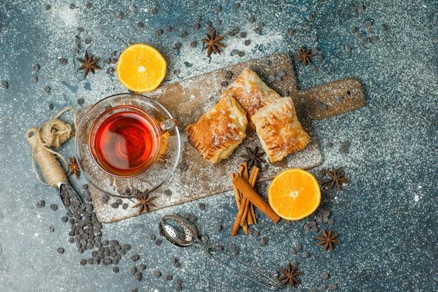 Pasteles con harina, té, naranja, choco chips, especias en estuco y tabla de cortar, vista superior.