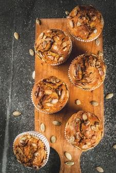 Pasteles horneados en otoño e invierno muffins de calabaza saludables con especias tradicionales de otoño semillas de calabaza mesa de piedra negra