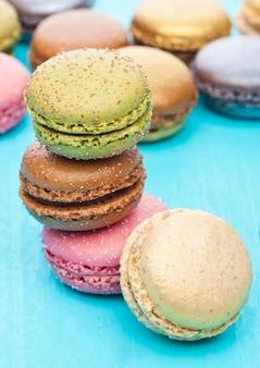 Pasteles de macarons coloridos de lujo francés sobre fondo de madera azul con azúcar en la parte superior