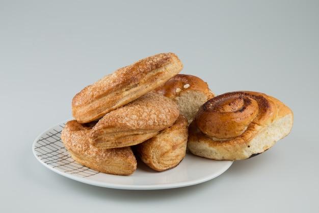Pasteles y pan en un plato aislado en superficie blanca