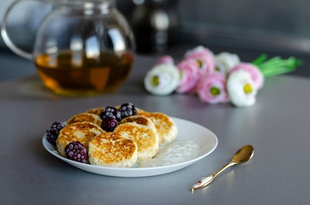 Pasteles de queso de requesón con moras en mesa gris con tetera transparente, cuchara de té y flores