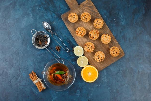 Pasteles de relleno de gelatina en una tabla para cortar con una taza de té, coladores de té, especias y frutas cítricas